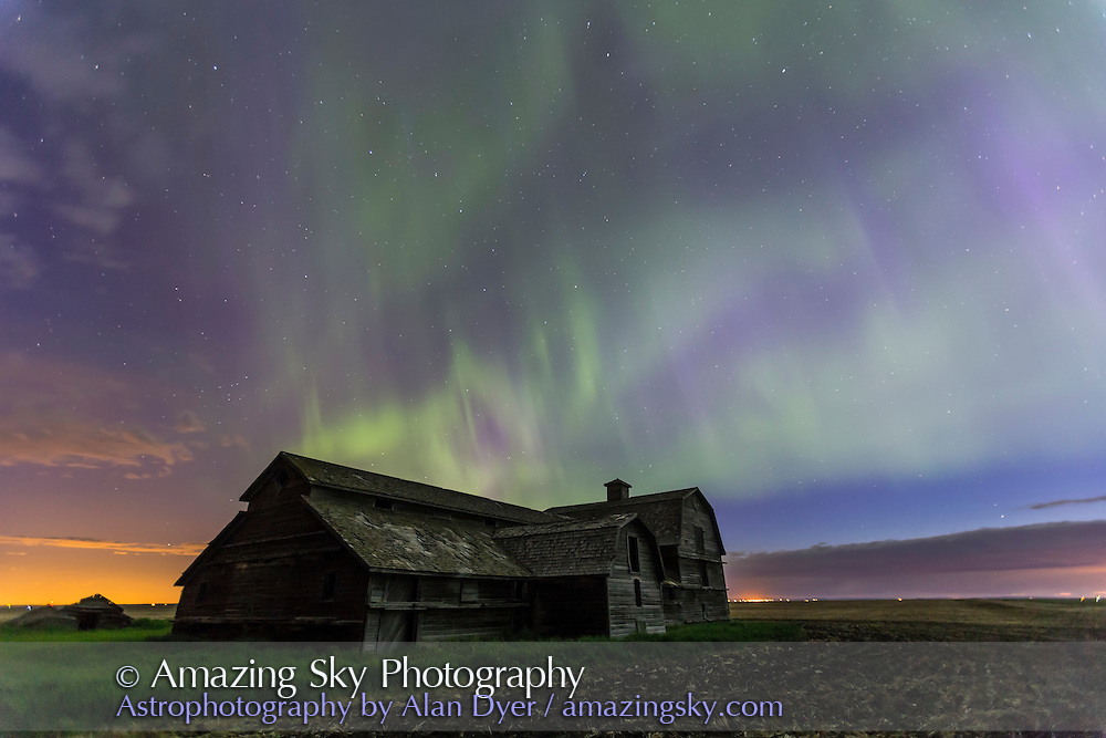 An all-sky aurora with green and purple curtains, the night of June 7-8, 2014, starting up about 12:30 and going until dawn. This shot was as it declined in colour and brightness, and was taken from the old barn site near home in southern Alberta. Foreground illumination is from the aurora and ambient sky -- the Moon had set but morning dawn was coming on. The Big Dipper is above the Barn. The purple colour is from blue scatttered sunlight hitting the red tops of the auroral curtains. This was with the 16-35mm lens at f/2.8 for 20 seconds at ISO 800 with the Canon 6D.