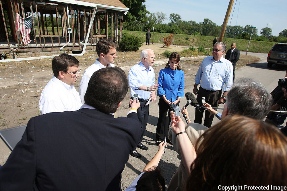 Iowa House Member Kraig Paulsen (R-IA35), Cedar Rapids City Council member Brian Fagan, US Republican US presidential nominee Senator John McCain (R-AZ), his running mate Alaska Govenor Sarah Palin, and John Smith, owner of CRST, (from left) outside a flood damaged house on O Avenue after a campaign rally in Cedar Rapids, Iowa, September 18, 2008.