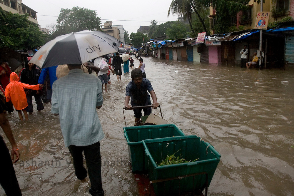 People walk through a flooded road in Mumbai, India, on Friday July 1, 2008. Photographer:  Prashanth Vishwanathan/Bloomberg News