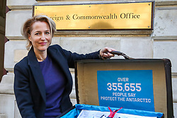 © Licensed to London News Pictures. 9/10/2018. London, UK. Gillian Anderson poses outside Foreign & Commonwealth Office with a petition signed by 2 million people globally (350,000 in the UK) calling for the creation of the largest protected area on Earth – a 1.8 million square kilometre Antarctic Ocean Sanctuary. Gillian Anderson is accompanied by Greenpeace's campaigners and a penguin sculptures which have appeared in cities around the world 'marching' for protection. Photo credit: Dinendra Haria/LNP