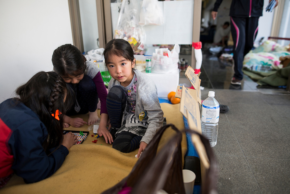 KUMAMOTO, JAPAN - APRIL 20: A family, survived from earthquake, play on early morning on April 20, 2016 in Mashiki Gymnasium evacuation center, Kumamoto, Japan. As of April 45 people were confirmed dead after strong earthquakes rocked Kyushu Island of Japan. Nearly 11,000 people are reportedly evacuated after the tremors Thursday night at magnitude 6.5 and early Saturday morning at 7.3.<br />