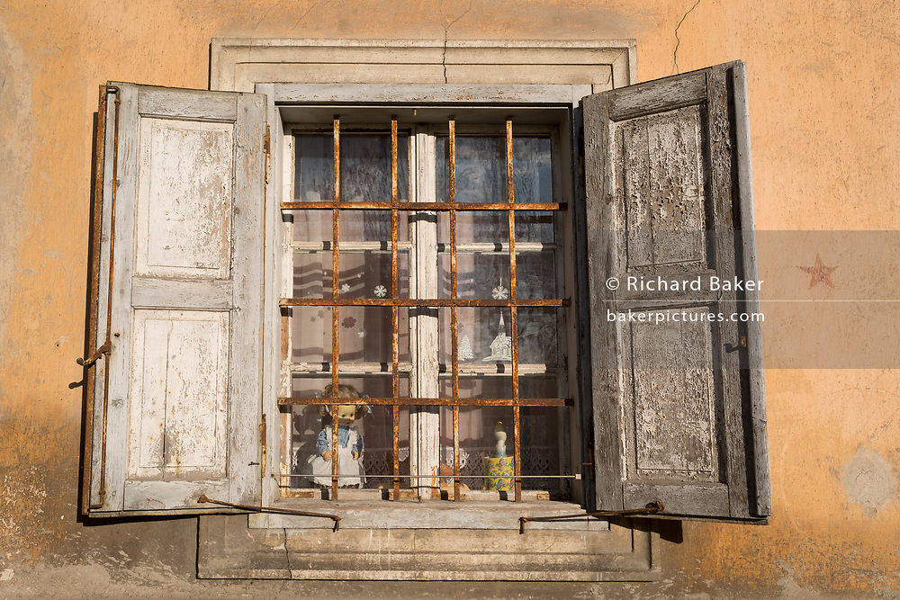 Old windows with a child's doll inside, of a Slovenian village house on 18th June 2018, in Bohinjska Bela, Bled, Slovenia.