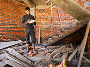 02 MARCH 2017 - SANKHU, NEPAL: A construction worker scavenges wood for a home he is working in Sankhu. Many of the homes are being rebuilt with materials scavenged from buildings destroyed in the 2015 earthquake, There is more construction and rebuilding going on in Sankhu, west of central Kathmandu, than in many other parts of the Kathmandu Valley nearly two years after the earthquake of 25 April 2015 that devastated Nepal. In some villages in the Kathmandu valley workers are working by hand to remove ruble and dig out destroyed buildings. About 9,000 people were killed and another 22,000 injured by the earthquake. The epicenter of the earthquake was east of the Gorka district.   PHOTO BY JACK KURTZ