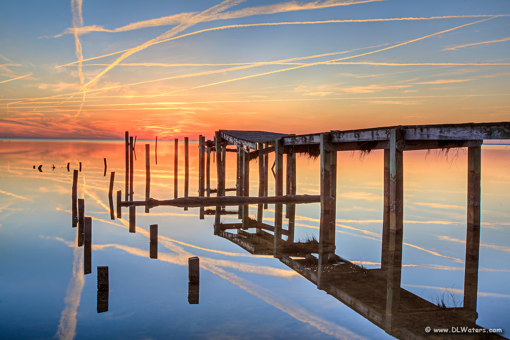 Reflection of a destroyed boat dock on Currituck sound at sunset.