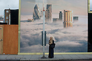 A Muslim lady awaits a bus beneath a property developer's billboard showing a large aerial image of London skyscrapers in low cloud.