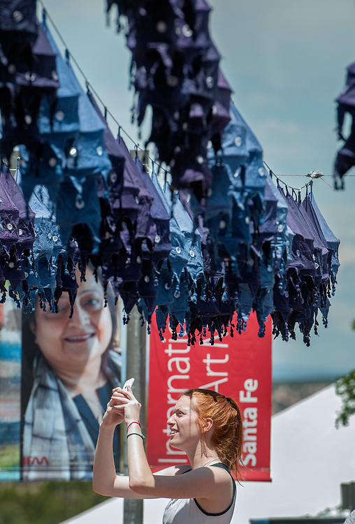 em071217a/b/Sofia Miller, 17, a volunteer from Milwaukee Wis., takes a picture of the dozens of hand dyed and made lanterns hanging on Museum Hill in Santa Fe for the 2017 International Folf Art Marker. They were among around 2000 volunteers that were helping with the market this year. The event starts Thursday and runs through the weekend but the main public events are Saturday and Sunday with 160 artist from 53 countries.   (Eddie Moore/Albuquerque Journal)