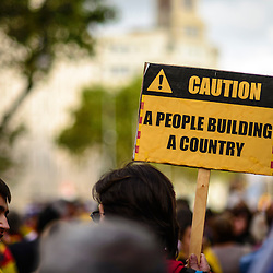 "A protest sign that looks like a constructions sign reads, ""Caution, A people building a country"" during the National Day of Catalonia."
