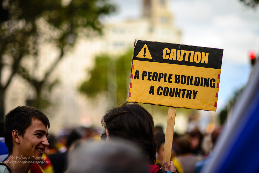 """A protest sign that looks like a constructions sign reads, """"Caution, A people building a country"""" during the National Day of Catalonia."""