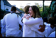 Girl and boy hug, reunited at parade of the blue Obby Oss during Padstow's May Day fest; Cornwall, England.
