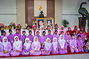 26 NOVEMBER 2012 - BANGKOK, THAILAND:   Muslim school children pose in front of picture of the King and Queen of Thailand after paying their respects to the monarchy at Siriraj Hospital in Bangkok. Siriraj was the first hospital in Thailand and was founded by King Chulalongkorn in 1888. It is named after the king's 18-month old son, Prince Siriraj Kakuttaphan, who had died from dysentery a year before the opening of the hospital. It's reported to one of the best hospitals in Thailand and has been home to Bhumibol Adulyadej, the King of Thailand, since 2009, when he was hospitalized to treat several ailments. Since his hospitalization tens of thousands of people have come to pay respects and offer get well wishes. The King's 85th birthday is on Dec 5 and crowds at the hospital are growing as his birthday approaches. The King is much revered throughout Thailand and is seen as unifying force in the politically fractured country.      PHOTO BY JACK KURTZ