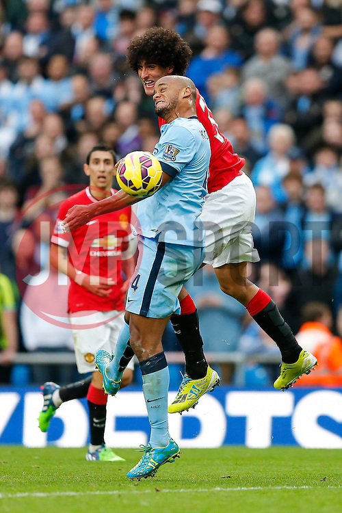 Vincent Kompany of Manchester City and Marouane Fellaini of Manchester United compete in the air - Photo mandatory by-line: Rogan Thomson/JMP - 07966 386802 - 02/11/2014 - SPORT - FOOTBALL - Manchester, England - Etihad Stadium - Manchester City v Manchester United - Barclays Premier League.