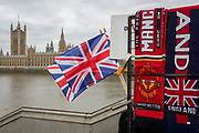 The Union Jack and football scarves on sale in a tourists' kiosk overlooking the Houses of Parliament across the river Thames in Westminster, on 27th March 2019, in London, England