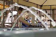 Framed by the fountain effect of one spa, Sally Westover, from Centerville talks with Jeff Roggenbeck, from Springfield about another one in the Knickerbocker Pools & Spas booth, during Miami Valley HomeWorld, at the Dayton Exposition Center in Vandalia, Saturday, February 10th.