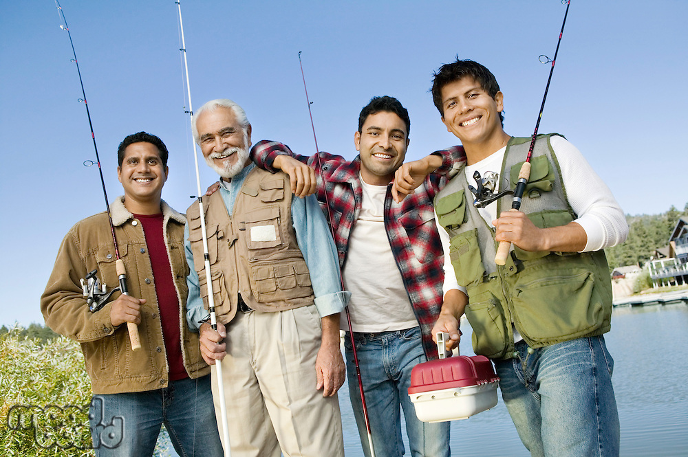 Middle-aged man with three sons holding fishing rods smiling (portrait)