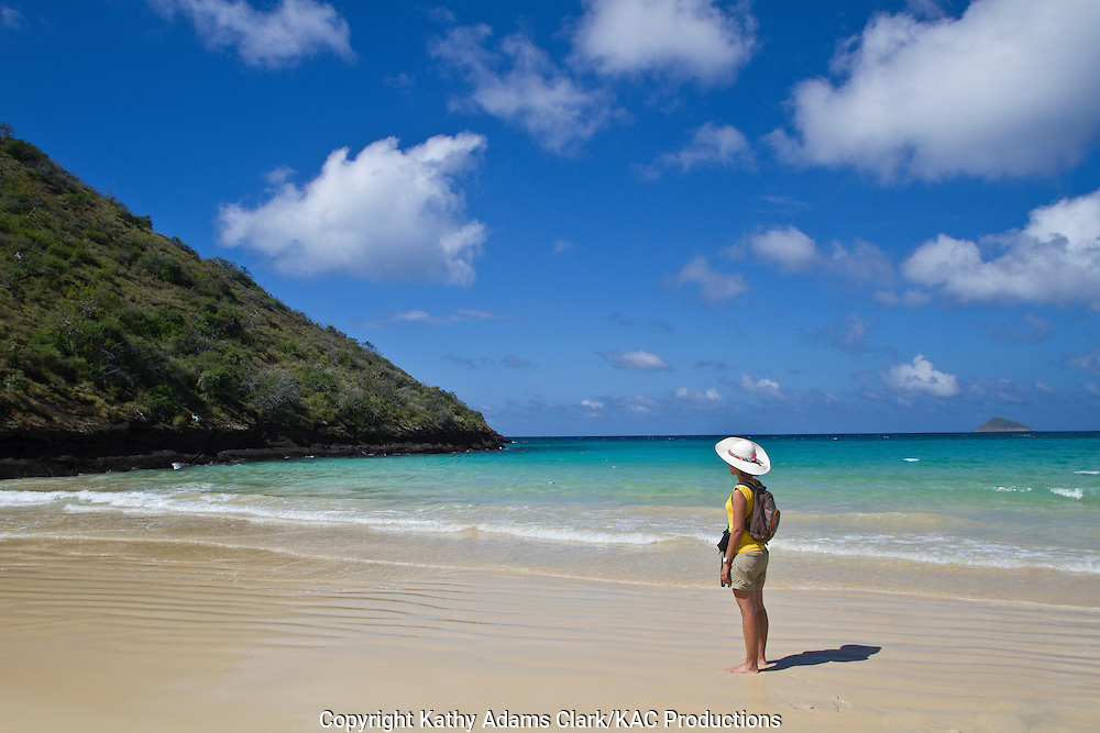 Female tourist, walking along the white sand beaches of Cormorant Point, on Floreana Island, Galapagos, Ecuador
