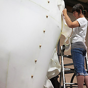 One of the technical crew works on shaping the hind leg of the bear. Aurora is a giant polar bear puppet, the size of a London double decker bus. The bear is the brain child of Greenpeace UK and it will be the center piece in the Greenpeace campaign Save the Arctic  global day of action in London Sept 15th. Aurora is designed by Christopher Kelly in collaboration with props designer Simon Costin and made by Factory Settings in East London.