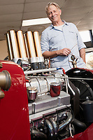Close up of car engine with happy senior man standing behind