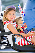 A young girl wearing patriotic costume holds here American Girl doll during the I'On neighborhood Independence Day parade July 4, 2015 in Mt Pleasant, South Carolina.