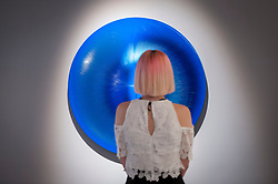 "© Licensed to London News Pictures. 28/06/2018. LONDON, UK. A visitor poses against ""Dinamica celeste e blu"", 2006, by Alberto Biasi.  Members of the public visit Masterpiece London, the world's leading cross-collecting art fair held in the grounds of the Royal Hospital Chelsea.  The fair brings together 160 international exhibitors presenting works from antiquity to the present day and runs 28 June to 4 July 2018.  Photo credit: Stephen Chung/LNP"