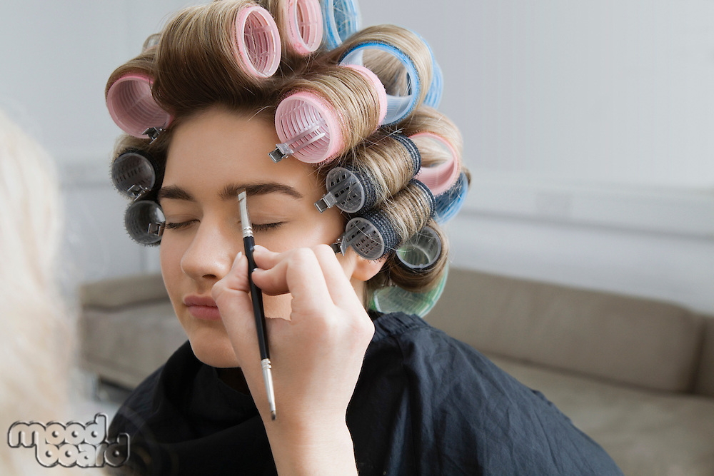 Model in Hair Curlers Having Makeup Applied