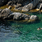 The Mediterranean Sea boasts many aqua-marine swimming holes that tourists and locals swim in daily. A couple swims in the clear blue waters in the Cinque Terre.