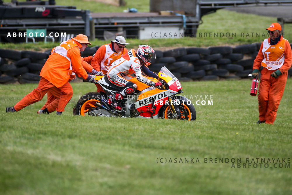 Marc Marquez riding for Repsol Honda Team  gets his bike pushed by marshall's after crashing out during the 2014 MotoGP of Australia at Phillip Island Grand Prix Circuit in Phillip Island, Australia.  Photo Asanka Brendon Ratnayake