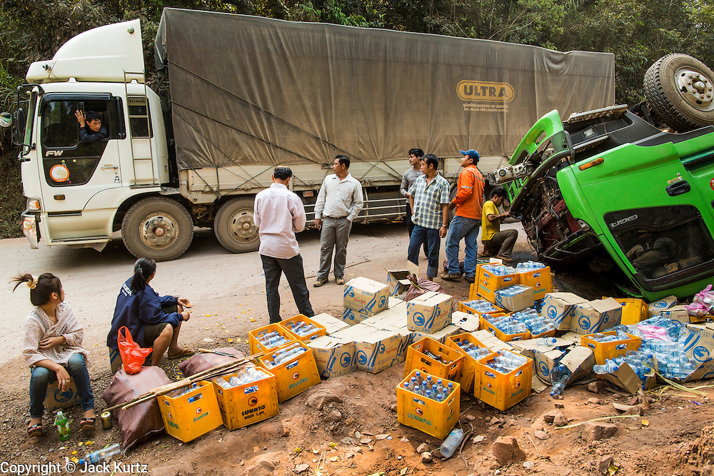 15 MARCH 2013 -  OUDOMXAY, LAOS: A truck hauling goods from Thailand to China on Highway 13 in rural Laos passes an overturned Beer Lao truck on the road. People were hired to salvage the beer that didn't pop open when the truck overturned. PHOTO BY JACK KURTZ