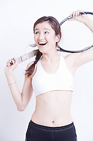 Young Asian woman holding tennis racket over her shoulder against white background