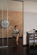 Business woman reading paper sitting in office doorway