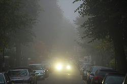 © London News Pictures. 16/10/2013. London, UK.  A car using fog lights in the early morning on a residential street at a fog covered  Hempstead in North London. Parts of the UK have woken to thick fog this morning. Photo credit: Ben Cawthra/LNP
