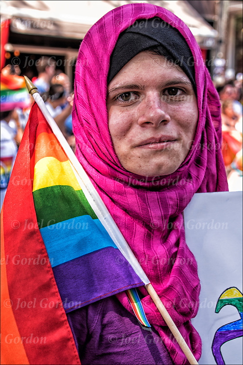 Lesbian Muslim Pride marcher in the Gay Pride Parade showing her pride poses for the camera.