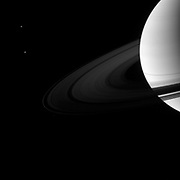A pair of Saturn's moons accompany the planet and its rings. Dione is in top left and Tethys is below. Cassini.