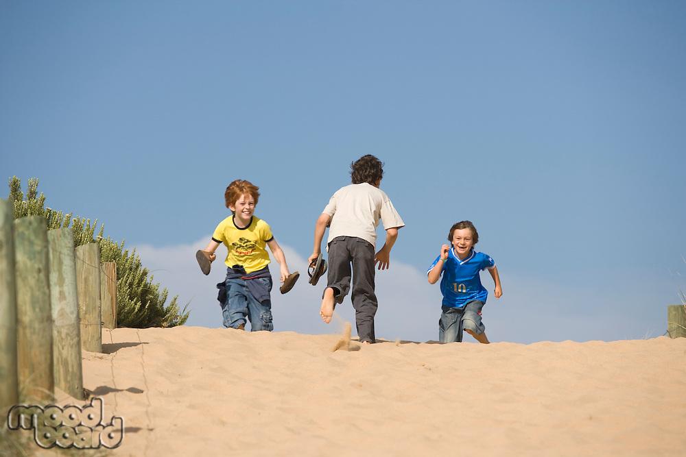 Three pre-teen boys running towards beach
