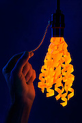 A hand pulling on the chain to a light socket holding glowing ribbon.Black light