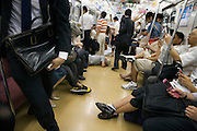 homeless man sleeping on the floor of a commuter train with passengers Japan