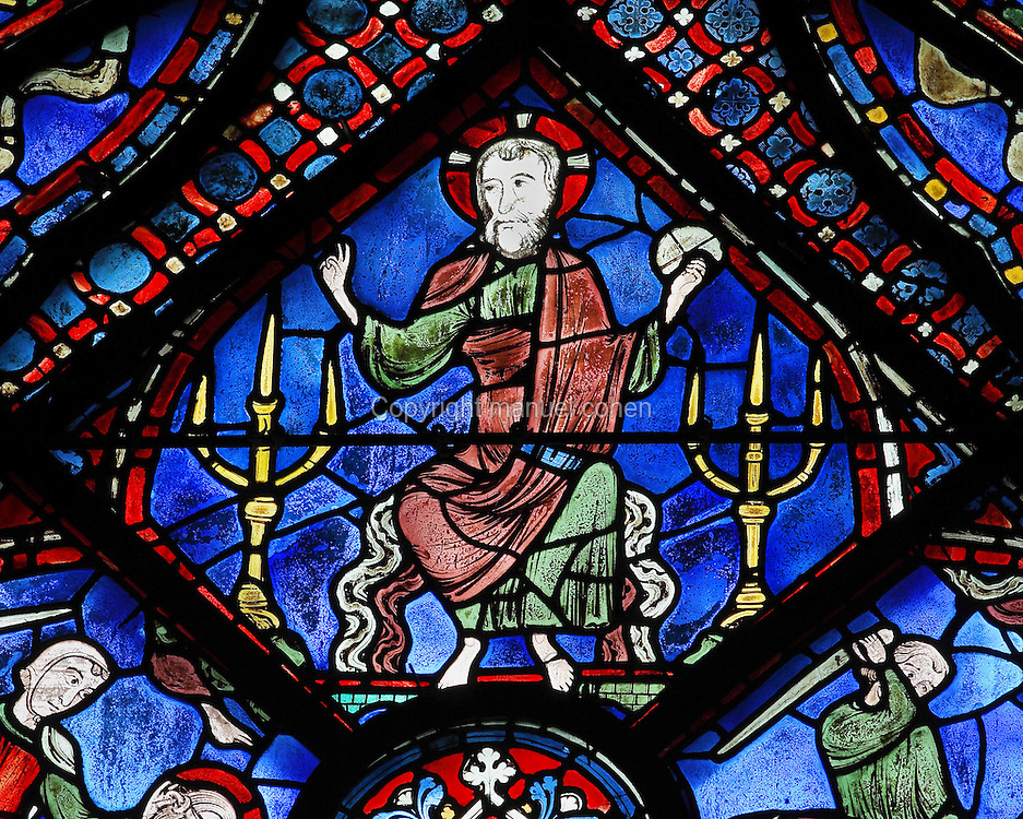 Christ is sitting on a cloud above the arch of a bridge, with 2 candelabra. He holds the globe of the earth in his left hand and with his right, blesses the 2 martyrs, Josiah and James. Section of Christ blessing, 1210-25, at the apex of the Life of St James window in the ambulatory of Chartres Cathedral, Eure-et-Loir, France. This window tells the story of the life of St James the Greater, apostle of Jesus and son of Zebedee. It is situated next to the apostles chapel. Chartres is a stop on the pilgrimage route to Compostela, where James' relics lie. Chartres cathedral was built 1194-1250 and is a fine example of Gothic architecture. Most of its windows date from 1205-40 although a few earlier 12th century examples are also intact. It was declared a UNESCO World Heritage Site in 1979. Picture by Manuel Cohen