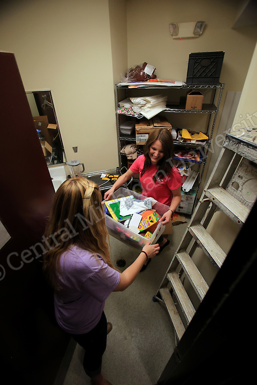 Site co-leader Stephanie Ralls, of Belleville, (left)  grabs contents of closet from Hannah Long, of Waterford, as they clean and organize it. They were among eleven CMU students volunteering during her Alternative Break at the Carolina Youth Development Center in North Charleston, SC, spending the week to help with projects to improve the center and in the community.  CMU is ranked fourth in the nation for the number of students participating in Alternative Breaks and fifth in the country for the most trips coordinated by a university. The program organizes about 40 trips each year with more than 400 students participating. Photo by Steve Jessmore/Central Michigan University