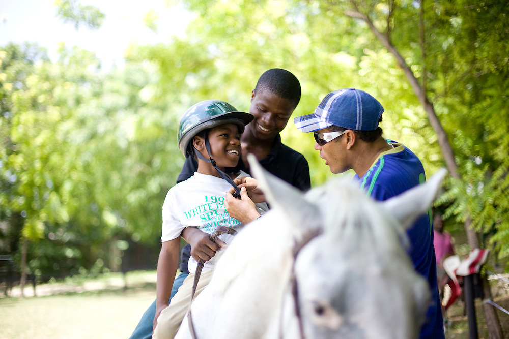 Equestrian Club employee Normandy Chery holds onto Josephine Michel, age 9, (all the chilren's last names are Michel because that is the name of the orphanage director) as Paco Gonzales tightens Josephine's helmet during an equestrian therapy session with Athletic Club Centre Equestre. For two years Gonzales has been doing equestrian therapy with young people with disabilities from the Wings of Hope orphanage in Fermathe. Gonzales, formally a professional horse jumper, was inspired to start doing equestrian therapy after an accident left him unable to walk for two years. Gonzales says the children have been transformed by the horse riding and some have become more emotionally stable. One of the children, Vivian Michel, has improved her ability to walk. All of the children have learned how to ride.