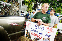 Bill Ross, a handler with Wolf People in Cocolalla, waits with his protest sign to attract the attention of Gov. Butch Otter during a barbecue Wednesday in Spirit Lake.