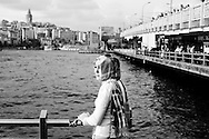 A young lady waits near Galata bridge in Istanbul