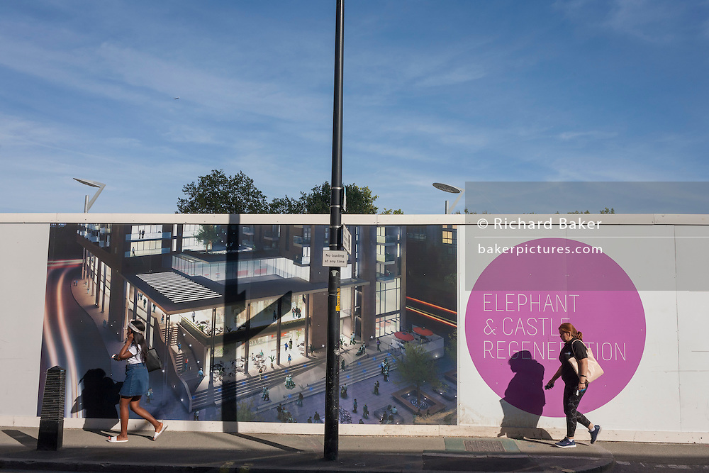 Locals walk past a construction hoarding showing the future regenerated development at Elephant & Castle, south London.