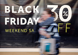 """© Licensed to London News Pictures. 25/11/2016. London, UK. A woman walks past a 30% off sale sign on Oxford Street, central London on """"Black Friday"""". Sales from this years Black Friday event are expected to top £2 billion. Photo credit: Tolga Akmen/LNP"""