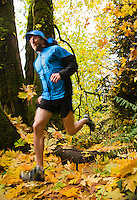 A man trail running in the forest in Fall colors.