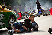 14 MAY 2010 - BANGKOK, THAILAND: Red Shirt protesters take cover on Rama IV Road in Bangkok after troops fired toward them at the intersection of Rama IV and Witthayu Roads in Bangkok Friday morning. The protesters started the incident by firing rockets and throwing rocks at the troops. Tensions among Red Shirt protesters demanding the dissolution of the current Thai government rose overnight after Seh Daeng, the Red Shirt's unofficial military leader was shot in the head by a sniper. Gangs of Red Shirts have taken over military checkpoints on Rama IV and are firing small rockets at military helicopters and army patrols in the area. Troops have responded by firing towards posters.  PHOTO BY JACK KURTZ