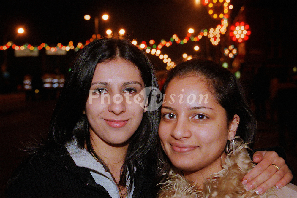 Two teenage girls standing together in street to celebrate Diwali; festival of light,