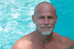 portrait of a middle aged man in a swimming pool