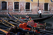 Gondolier steers his craft past a row of gondolas in canal in Venice, Italy..Subject photograph(s) are copyright Edward McCain. All rights are reserved except those specifically granted by Edward McCain in writing prior to publication...McCain Photography.211 S 4th Avenue.Tucson, AZ 85701-2103.(520) 623-1998.mobile: (520) 990-0999.fax: (520) 623-1190.http://www.mccainphoto.com.edward@mccainphoto.com