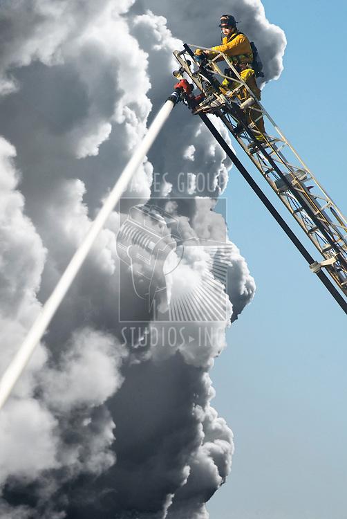 A Fire Man on a lift up high hosing a fire below him