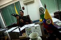 Colonel Moreno, the head of the police in Buenaventura, on the Pacific Coast of Colombia, shows his weapon in his office during an interview on Monday, May 14, 2007. Buenaventura is in the midst of a spree of violence over control of drug shipments from the poor barrios in the city. Many of the neighborhoods have a strong presence of FARC militias that control most of the drug trade in the city. (Photo/Scott Dalton)