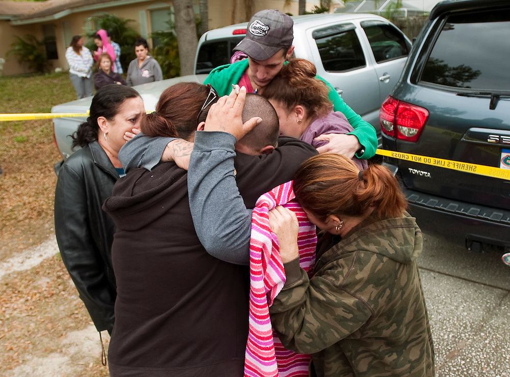 Jeremy Bush, center with hand on head, is embraced by his family and friends outside his home at 420 Faithway Drive in Seffner Friday, Feb. 1, 2013. Jeremy's brother Jeff, 36, was asleep Thursday night when a sinkhole opened in his bedroom, pulling him underground, authorities said.